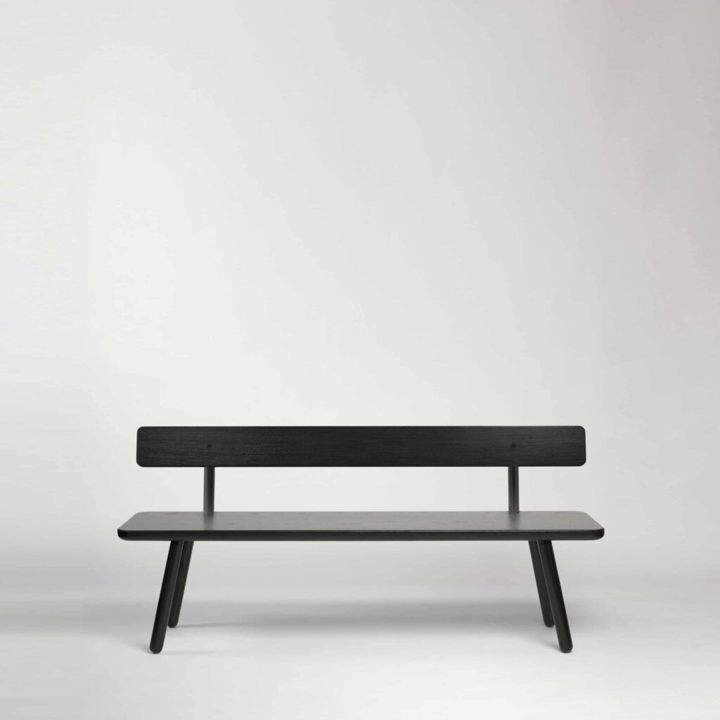 A black bench with back in black solid wood