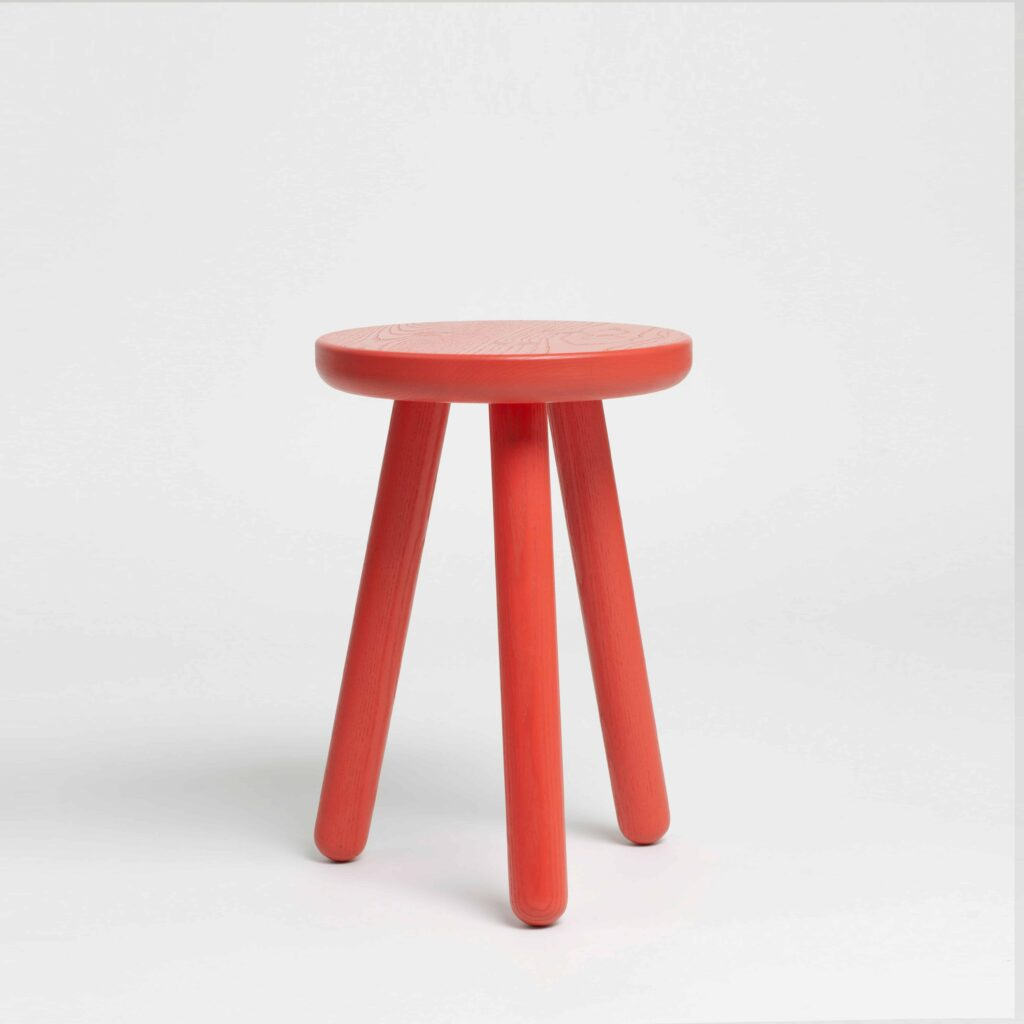 red three legged stool by another country